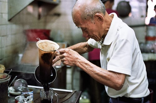 old uncle showing his skills in making traditional filter sock based coffee